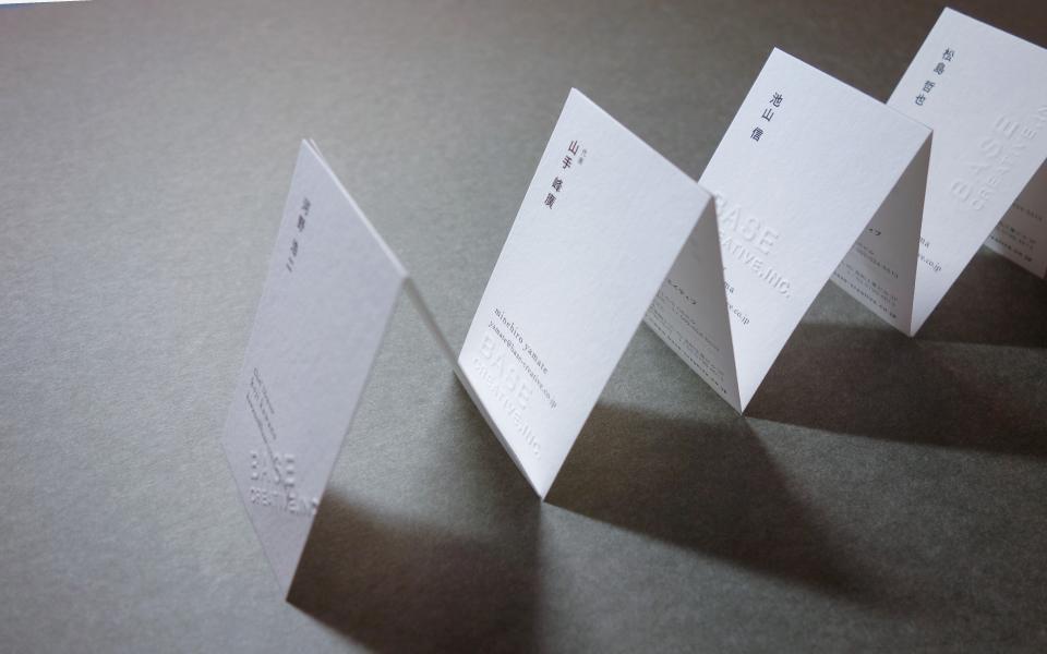 福岡のデザイン事務所namecard.福岡にあるデザインプロダクション/デザイン事務所の名刺。紙はわたがみを使用しEMBOSSERエンボッサーで自由な場所へエンボス加工