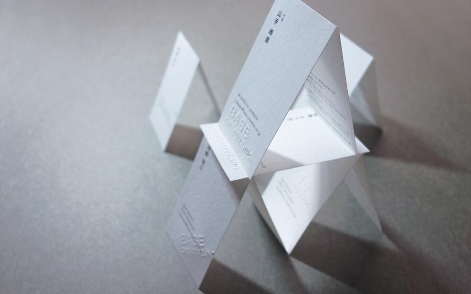 福岡にあるデザインプロダクションの名刺をピラミッドのように積んでいる