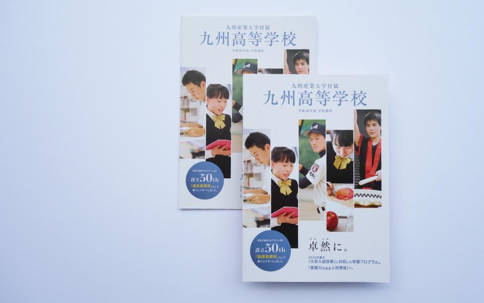 シンプルにデザインされた九州産業大学付属九州高等学校パンフレット。2冊ならべて撮影された学校案内パンフレット。