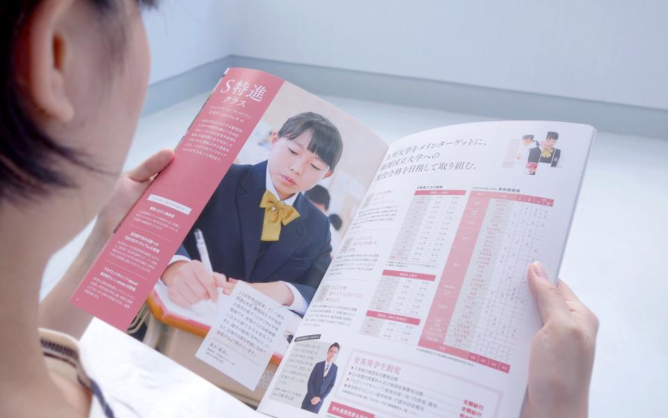 九州産業大学付属九州高等学校パンフレットデザインを手にとり、S特進クラスのページを読んでいる若い女性。