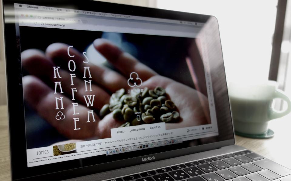 コーヒーを飲みながらMacbookのノートパソコンで、福岡市は六本松と今宿に2店舗展開している「世界一美味しい珈琲を提供したい」と初代が三和珈琲館を開店した「三和珈琲館のWEBサイト」のデザインをチェックしている。